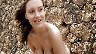 Busty brunette gets naked between two rock walls