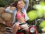 Pretty brunette is posing on the bike
