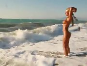 Stunning busty babe Ashley Bulgari enjoys the ocean waves with no clothes on