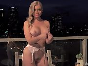 Curvaceous blonde Dorothy Grant posing on a balcony