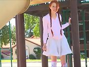 Naughty redhead Dolly reveals her puffy breasts and pink pussy on the playground