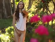 Busty young brunette strips and poses erotically outdoors