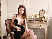 Petite young brunette Milla exposes a stunning pair of round and big boobs