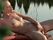 Adorable Sophie Lynx slowly rubs her pink muff by the lake
