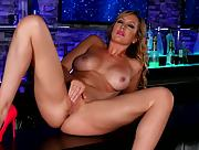 Busty and horny Brett Rossi fingers her beaver on the bar