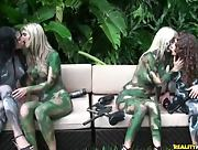 Stunning babes covered in camo paint make out after paintball