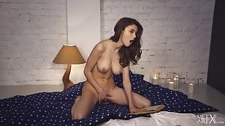 Lovely big titted brunette reads erotic novel and pleasures herself on the bed