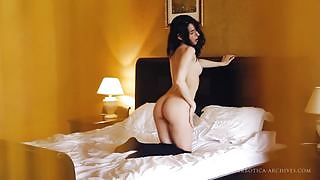 Incredibly sexy Irida lays on the bed in sexy stockings and teases her shaved pussy