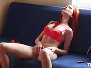 Redhead babe in sexy red lingerie rubs her sweet pussy on the couch
