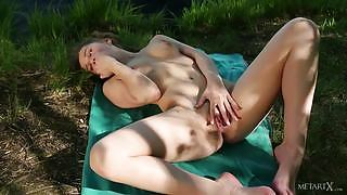 Charming young babe figers her moist pussy by the riverside