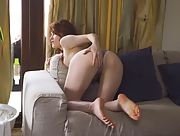 Astonishing redhead Jia Lissa spreads her legs on the sofa and rubs her pink pussy
