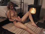 Girl with nice natural body masturbates in the bedroom by the fireplace
