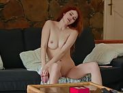 Fabulous redhead vixen Adel C relaxes on the sofa and strokes her tasty pussy