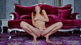 Skinny chick with small tits rubs her pussy by the violet couch