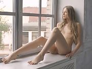 Slim and cute blonde Nimfa posing naked by the window
